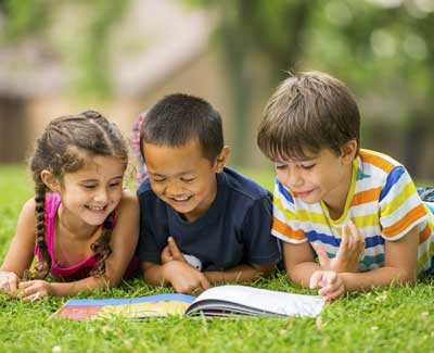 3 children reading outside